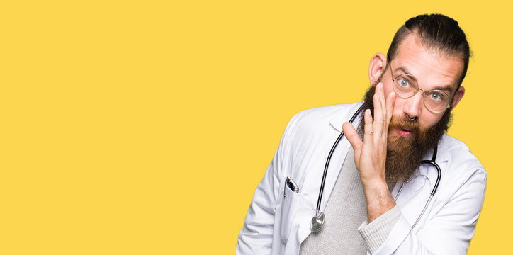 Young blond doctor man with beard wearing medical coat hand on mouth telling secret rumor, whispering malicious talk conversation
