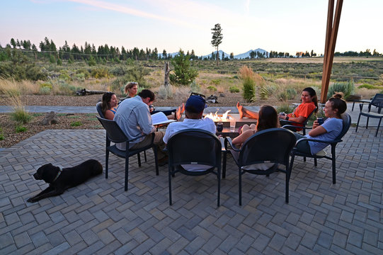 Six friends around a fire pit enjoy afternoon view of landscape around Sisters, Oregon on a perfect summer afternoon.