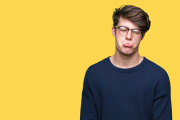 Young handsome man wearing glasses over isolated background depressed and worry for distress, crying angry and afraid. Sad expression.