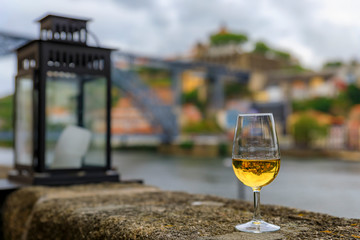 Glass of port wine with the blurred cityscape of Porto Portugal and a lantern in the background