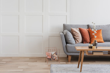 Copy space on empty white wall of fashionable living room interior with grey and orange design
