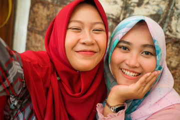 Happy and pretty Asian Indonesian girls in traditional Islamic hijab head scarf taking selfie together having fun at cafe in friendship and social media concept