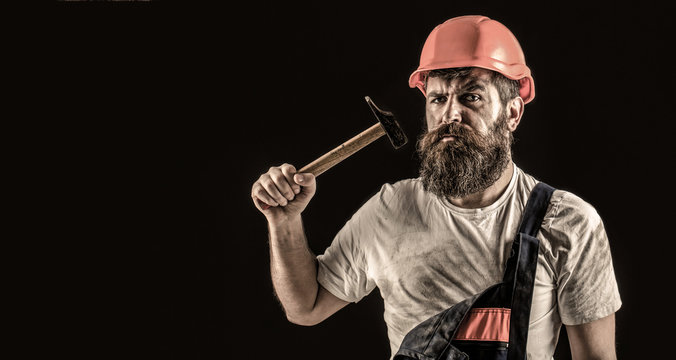Bearded builder isolated on black background. Bearded man worker with beard, building helmet, hard hat. Hammer hammering. Builder in helmet, hammer, handyman, builders in hardhat. Copy space