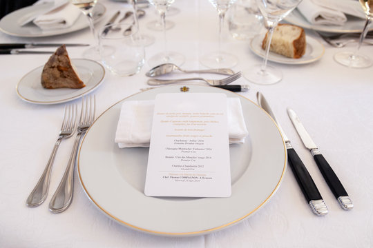 Closeup restaurant setting, porcelain plate, glasses, bread plate, knife, fork, printed white menu card, napkin. Concept gastronomic dinner, enjoy food and wine, tasting dishes, dinner from chef