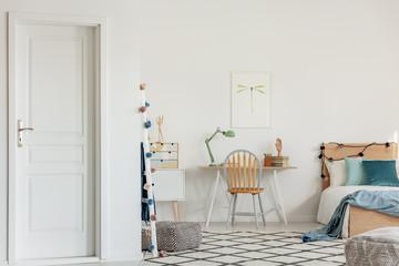 Wooden chair in front of scandinavian desk in elegant bedroom with home office