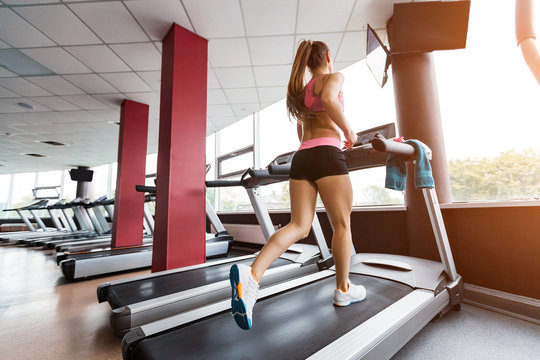 slim beautiful sporty girl running at the treadmill in the gym against sunset. Concept of cardio exercises and healthy way of life