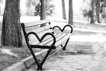 Bench heart for lovers in the park on the background. Black and White image
