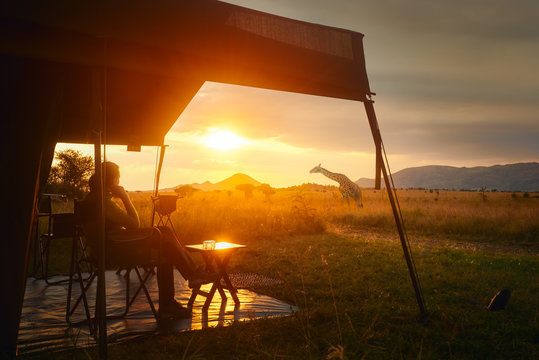Woman rests after safari in luxury tent during sunset camping in African savannah of Serengeti National Park,Tanzania.