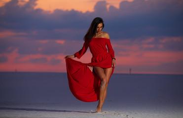 Beautiful fashion woman posing in maxi red dress on desert. Summer photo. Cloudy evening sky.