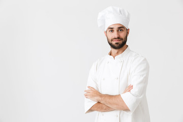 Concentrated young chef posing isolated over white wall background in uniform.