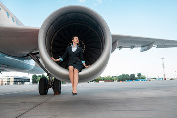 Beautiful young woman sitting near engine of airplane