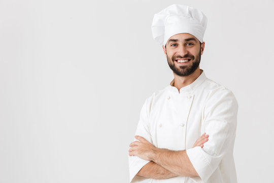 Young chef posing isolated over white wall background in uniform.