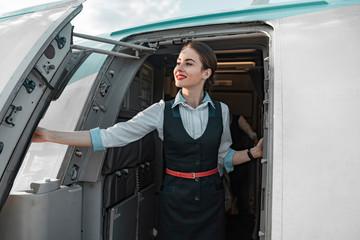 Attractive female flight attendant is on duty on board