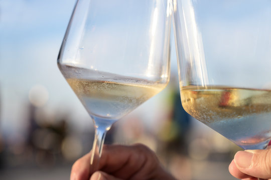 toast with cold white wine on a sunny summer evening during the holidays, concept for enjoyment and lifestyle, close-up