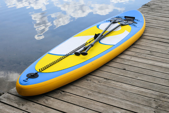 Close up of inflatable SUP board near river. Sup board, stand up paddle board