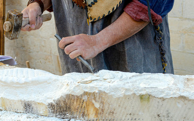 Stonemason With Ancient Costume During The Processing Of The Stone With Chisel