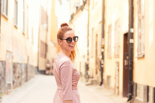 Smiling happy redhead woman looking back while walking on the empty street