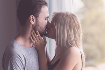 Couple hugging together. White youngman and woman standing near window with autum leafs in background. Kissing together. With light leaks.