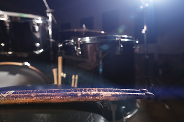 Close-up of used drumsticks lie on a drummer's chair against the background of a drum kit and flare of spotlights. The concept of music Fototapete