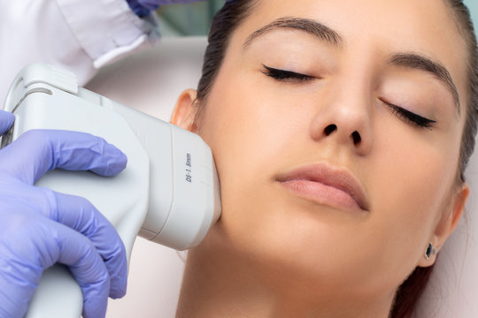 Top view of woman having facial hifu energy treatment.