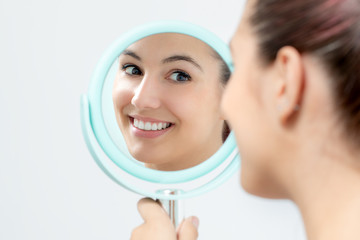 Young woman looking reviewing teeth whitening in mirror.