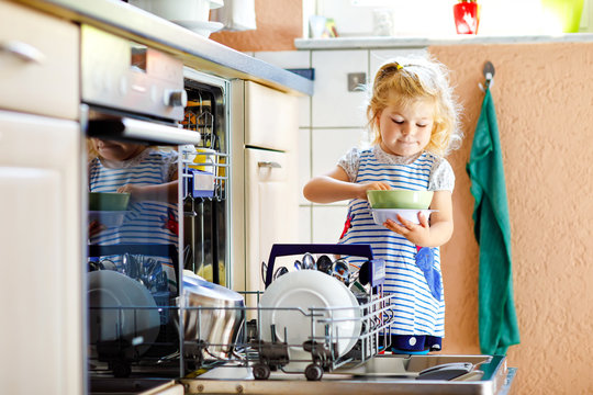 Little adorable cute toddler girl helping to unload dishwasher. Funny happy child standing in the kitchen, holding dishes and putting a bowl on head. Healthy kid at home. Gorgeous helper having fun