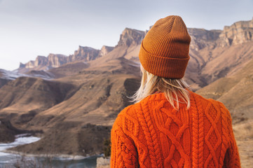 Portrait from the back of the girl traveler in an orange sweater and hat in the mountains against the background of a frozen mountain. Photo travel concept Fototapete