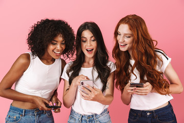 Smiling positive young three multiethnic girls friends posing isolated over pink wall background using mobile phones.
