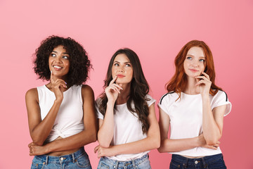 Thinking thoughtful cute multi-ethnic girls friends posing isolated over pink wall background.