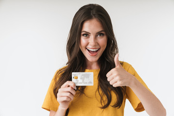 Image of gorgeous brunette woman wearing casual clothes showing thumb up and holding credit card