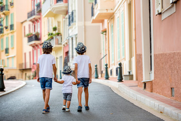 Children walking on a narrow street with houses in Monaco-Ville, Monaco on a cloudy day
