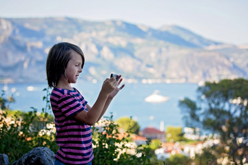 Preteen child, taking pictires with mobile of view on French Riviera