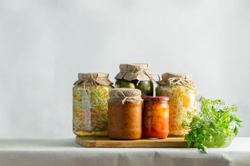 Fermented preserved or canning various vegetables zucchini sauerkraut carrots cucumbers in glass jars on table