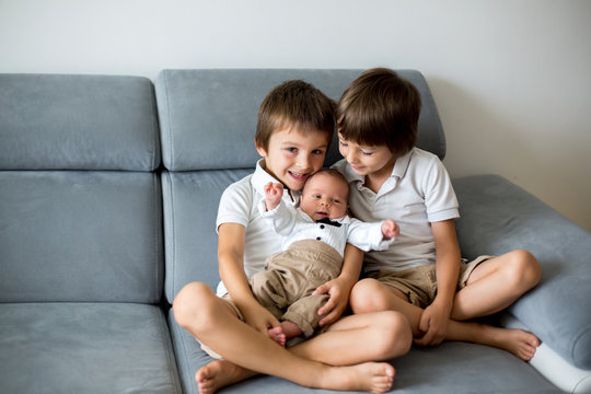 Sweet preschool boys, brothers, hugging with tenderness and care his little newborn brother