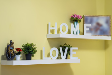 "White wooden signs ""HOME"" and ""LOVE"" on the shelves in the room."