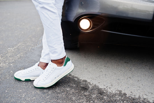 Close up sneakers in african man at white pants against car.