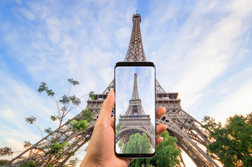 Hand holding the modern smartphone taking a picture of beautiful eiffel tower under blue sky, Eiffel Tower the most romantic tourist attraction and the symbol of Paris.