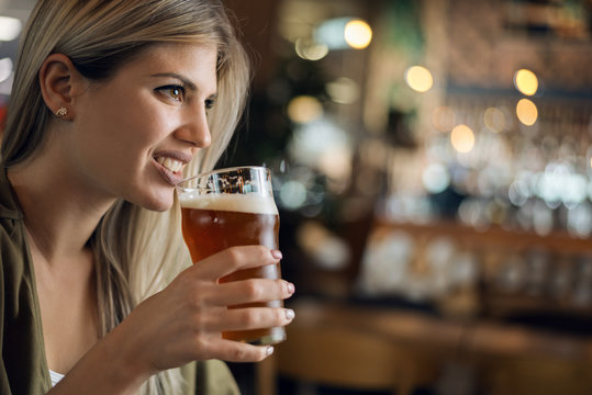 Close up of happy woman with glass of beer in a pub and looking away