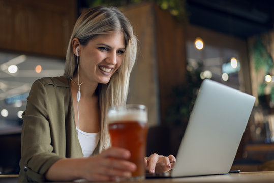 Happy young woman listening music over her laptop  in a bar
