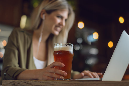Close up of unrecognizable happy woman holding glass of  beer while surfing the net on laptop in a bar