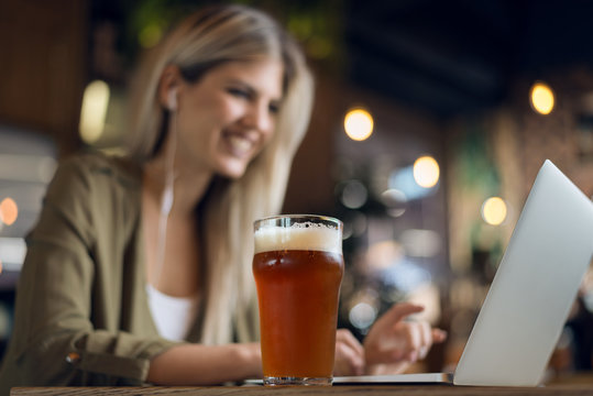 Close up of unrecognizable  happy woman working on her computer while relaxing in a bar.