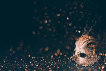 Luxury venetian mask on dark godlen bokeh background. New year and christmas party celebration design banner.