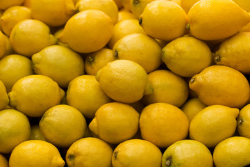 Fototapeta A pile of lemons at the vegetable market. Macro background of citruses.