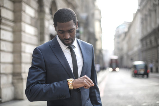 Businessman checking the time on his watch while walking in the street