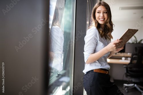 Wall mural Happy woman manager holding tablet and standing in modern office