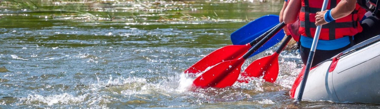 Rafting trip. Close up view of oars with splashes of water. Rowers make an effort to overcome the turbulent river. The concept of teamwork, healthy lifestyle.