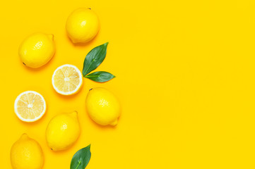 Wall Mural - Ripe juicy lemons and green leaves on bright yellow background. Lemon fruit, citrus minimal concept, vitamin C. Creative summer food minimalistic background. Flat lay, top view, copy space