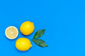 Wall Mural - Ripe juicy lemons and green leaves on bright blue background. Lemon fruit, citrus minimal concept, vitamin C. Creative summer food minimalistic background. Flat lay, top view, copy space