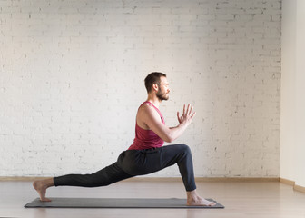 Warrior pose. Caucasian fit man stands in deep stretching and doing yoga in fitness studio, side view, selective focus.