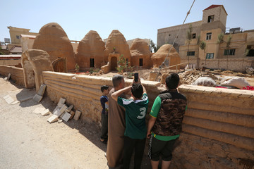 People take pictures of a mud house which Jordanian Hamad Nazzal built to raise people's awareness about the importance of protecting environment, in his hometown of Mafraq